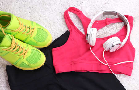 running pants: Sport clothes, shoes and headphones on white carpet background.