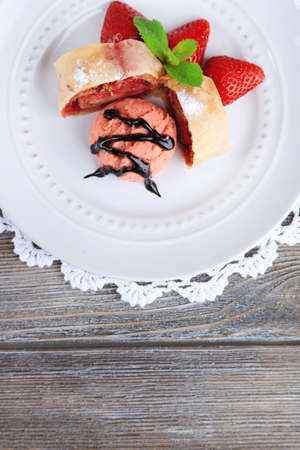 Tasty homemade strudel with ice-cream, fresh strawberry and mint leaves on plate, on wooden background photo