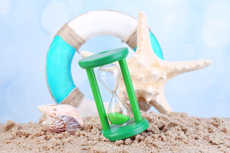Hourglass in sand on blue sky background photo