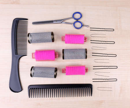 Professional hairdresser tools - comb, scissors and pins on light wooden background photo
