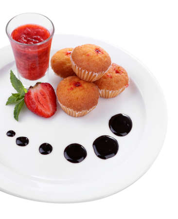 Tasty muffins with chocolate and red currant sauces on plate isolated on white photo