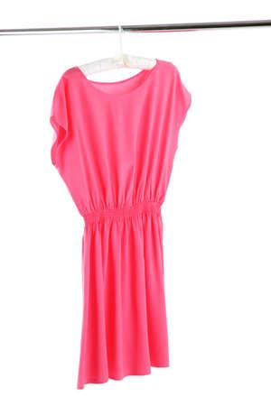 Vestido rosado hermoso que cuelga en perchas aislados en blanco