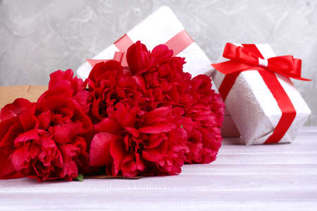 Beautiful pink peonies and gifts on wooden table photo
