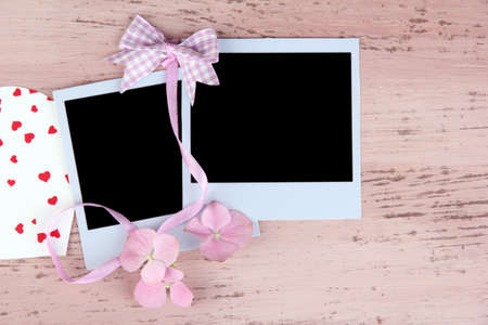 Blank old photos and decorative heart on color wooden background photo