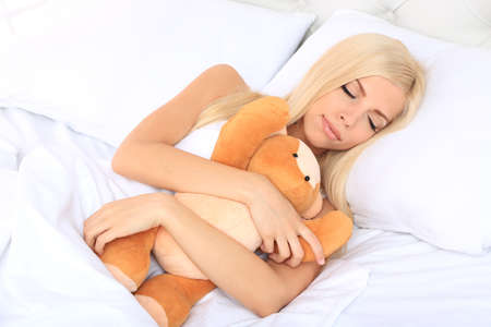 Young beautiful woman sleeping with teddy bear in bed photo