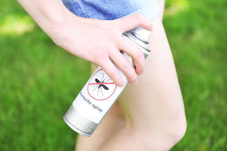 spray: Woman spraying insect repellent on skin, outdoor