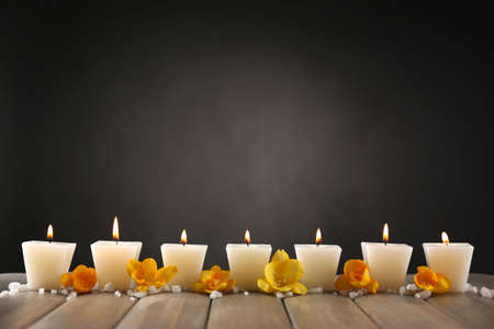Beautiful candles with flowers on wooden background photo