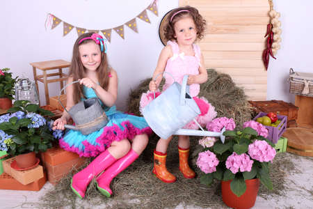 Beautiful small girls in petty skirts holding watering cans on country style background photo