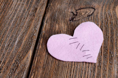 heartbreak issues: Broken heart and thread on wooden background
