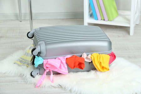 Suitcase with clothes on mat on room background photo