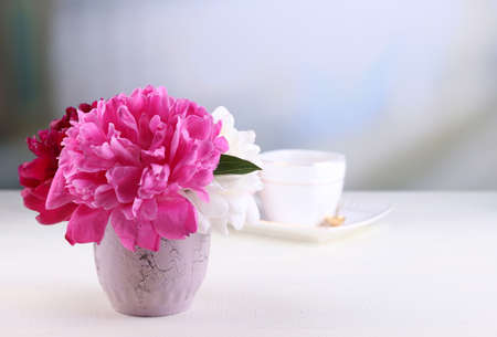 Composition of beautiful peonies in vase, tea in cup and marshmallow, on table, on light background photo