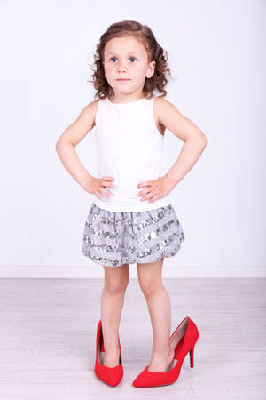 Beautiful small girl in big shoes on wall background