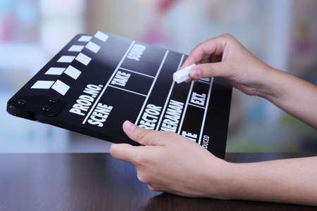 Black cinema clapper board in hands, close up photo