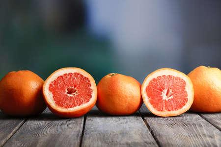 toronja: Pomelos maduros en la tabla de madera, en el fondo brillante