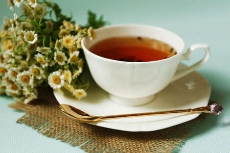 Cup of fresh herbal tea on table photo
