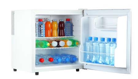 mini fridge full of bottles of juice, soda and fruit isolated on white photo