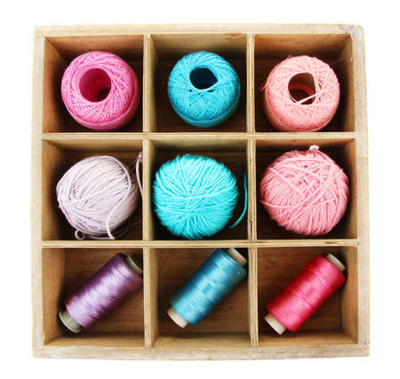 sewing box: Multicolored skeins of thread in wooden box isolated on white