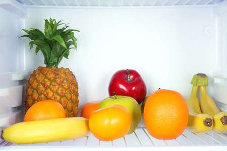 Fruits in open refrigerator. Weight loss diet concept. photo