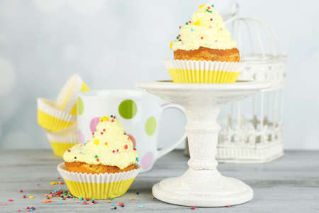 Tasty cup cakes with cream on grey wooden table photo