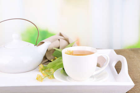 Tasty herbal tea with linden flowers on wooden table photo