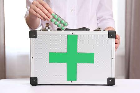 Enfermera que sostiene botiquín de primeros auxilios en la habitación