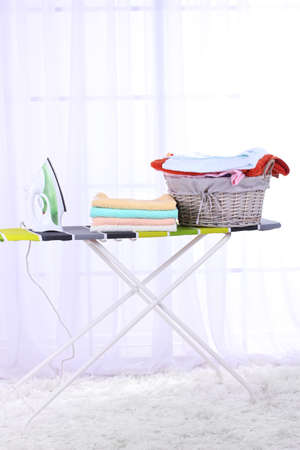 household tasks: Basket with laundry and ironing board on light home interior background