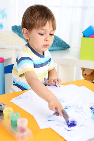 Cute little boy painting in room photo