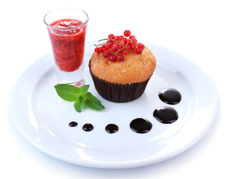 Tasty muffin with chocolate and red currant sauces on plate isolated on white photo