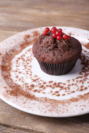 Chocolate muffin with red currant on plate on wooden background photo