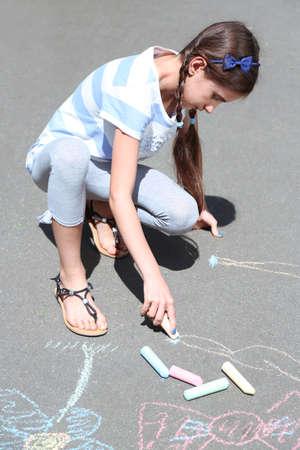 leggings: Cute girl drawing with chalk on asphalt