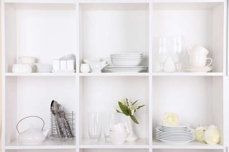Different white clean dishes on wooden shelves photo