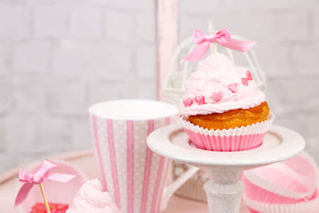 Tasty cup cake with cream on wooden chair photo