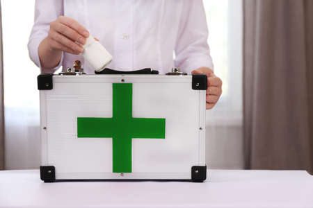 Nurse holding first aid kit in room photo