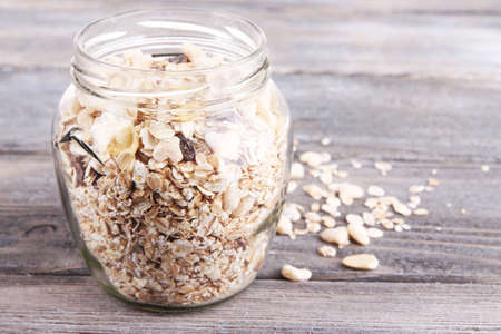 Homemade granola in glass jar, on color wooden background photo