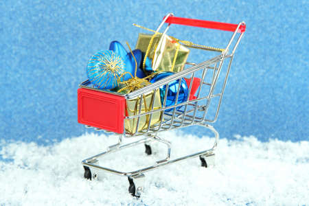 Christmas gifts in shopping trolley, on blue shiny background photo