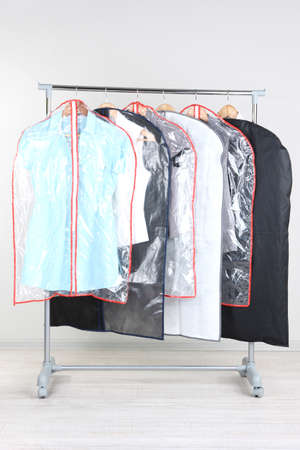 Office Female Clothes In Cases For Storing On Hangers, On Gray Background  Photo