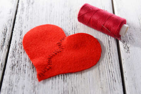 heart problems: Broken heart and thread on wooden background