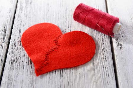 corazon roto: Roto el corazón y el hilo en el fondo de madera Foto de archivo