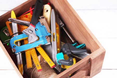 manual measuring instrument: Wooden box with different tools, on wooden background