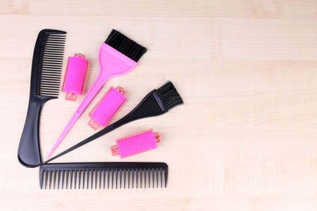 Professional hairdresser tools - comb, scissors and curlers on light wooden background photo