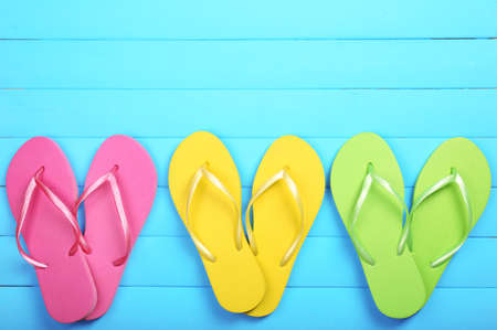 Bright flip flops on wooden background photo