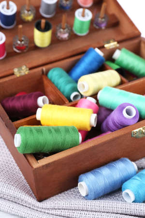 sewing box: Colorful threads for needlework in wooden box close up Stock Photo