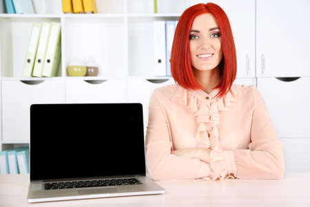 Young beautiful business woman with laptop in cabinet