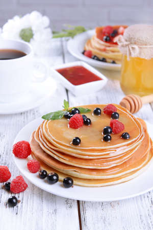 Sweet pancakes with berries on table close-up photo