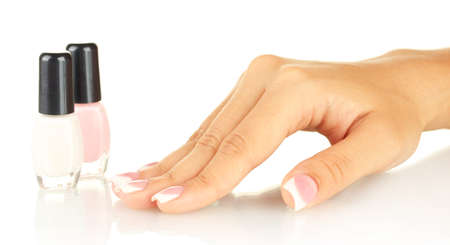 Beautiful womans hands with jars of nail polish, on white background photo