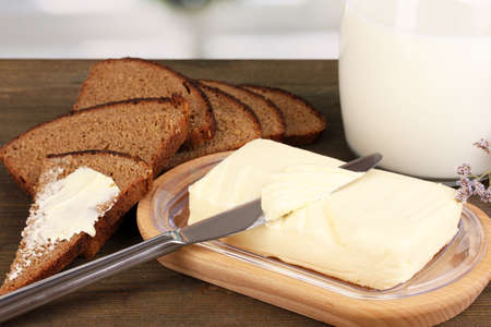 Butter on wooden holder surrounded by bread and milk on wooden table on window background photo