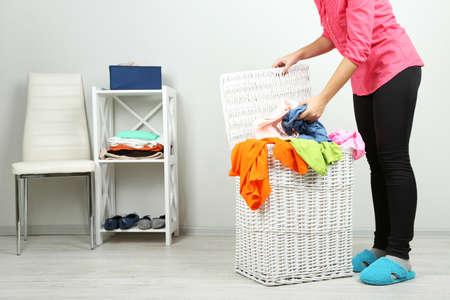 mimbre: Mujer con canasta de lavandería sobre fondo interior de una casa