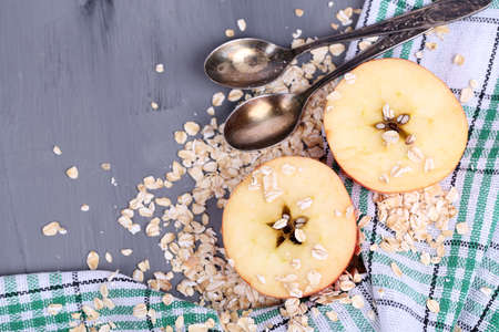 Apple with oatmeal and vintage spoons on napkin, on color wooden background photo