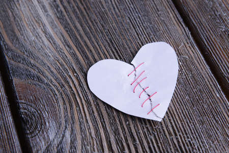 heartbreak issues: Broken heart and thread on wooden background