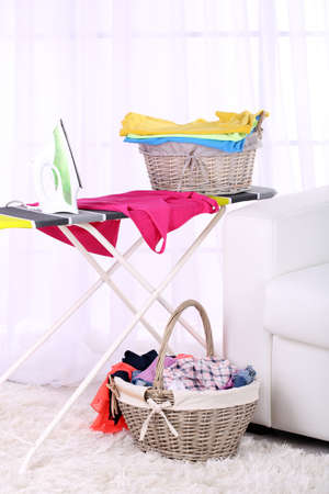 household tasks: Baskets with laundry and ironing board on light home interior background